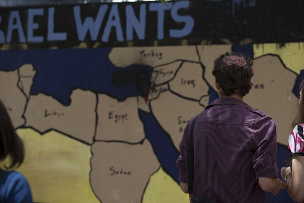 A student walks past the Israel Awareness Week mural which was defaced with black paint. Photo: Jay Caboz