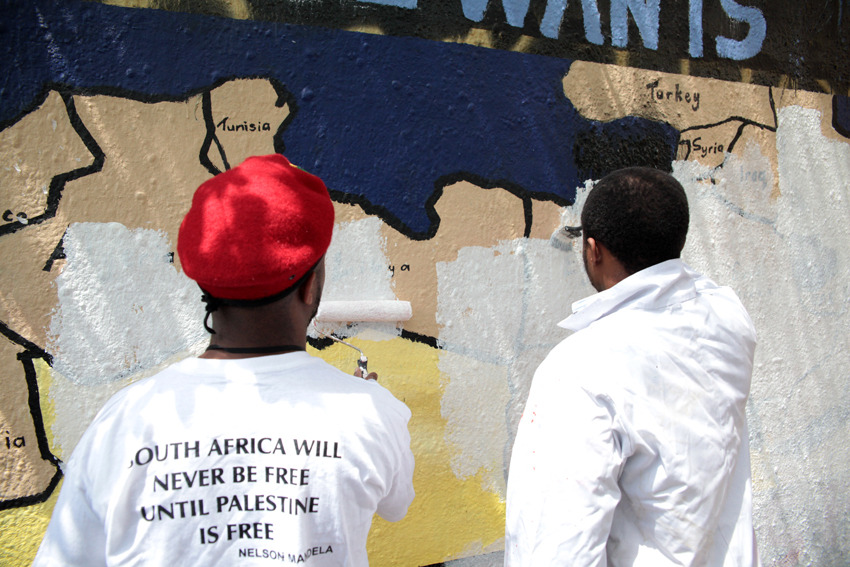 Wits SRC member Tokelo Nhlapo, in the red beret, and another student paint over the wall painted for Israel Awareness Week.