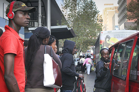 QUEUING QUEST: Commuters wait to catch a ride on the next taxi in Jorrisen Street. Other waiting commuters decided to rather take one of the working Metro buses (Background). Photo: Mia Swart
