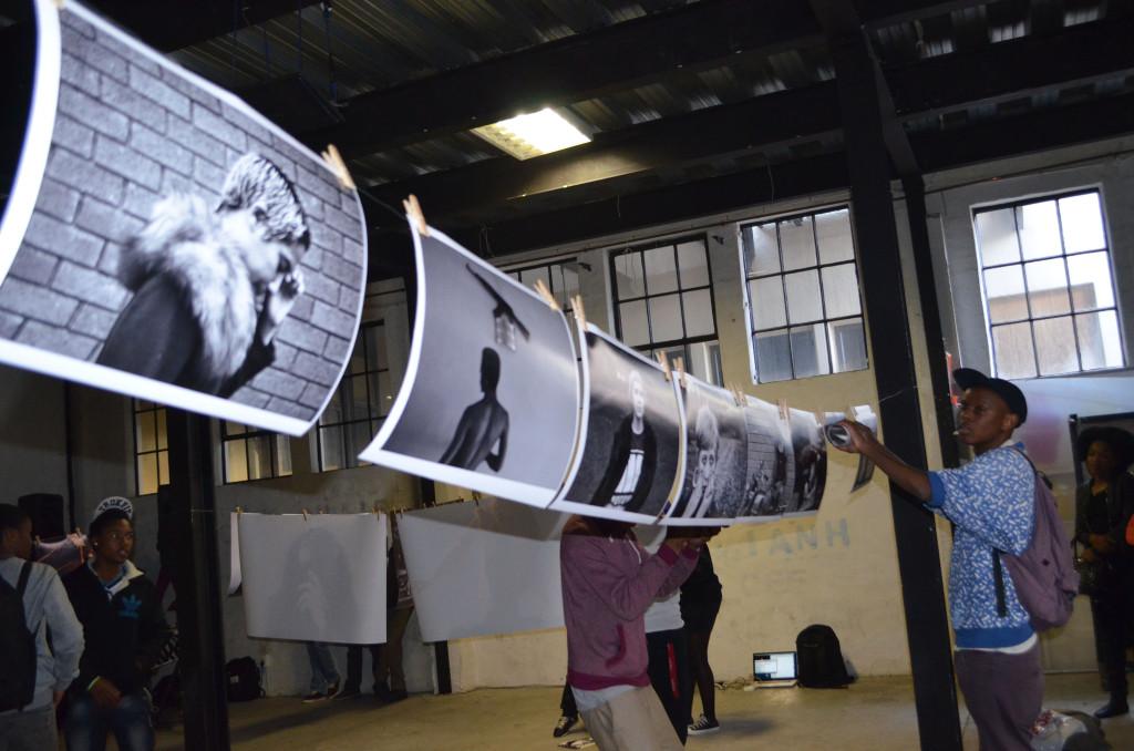 Brian Molepo hanging up his black and white portraits. Pheladi Sethusa