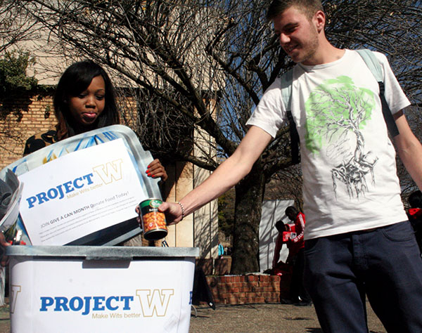 Ethan Genende Donates a can of beans in the Project W donation Bin outside the matrix.