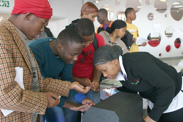 KEEP YOUR HANDS CLEAN: Students scan their hands for germs before having a meal at the dining hall.  Photo: Dineo Bendile