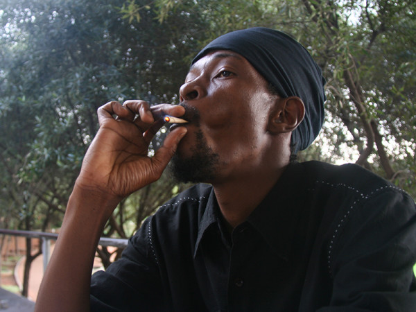 "PEACE,LOVE : RAS member Terrance Nzuza prefering to smoke a beedi (Indian-style tobacco wrapped in a leaf) rather than marijuana.  He said Rastari culture was not all ""pot-smoking and reggae. ""                                Photo: Mfuneko Toyana"