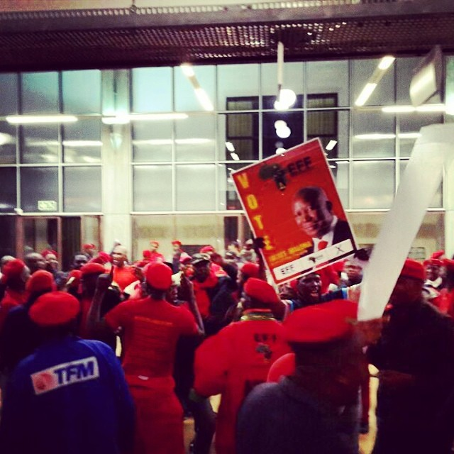 About 100 #EFF supporters sing outside the #Wits #GreatHall before the start of today's #greatdebate.