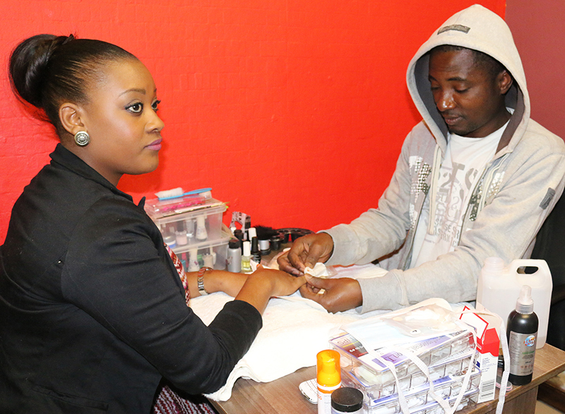 MAKING A LIVING: Immanuel Adu has been in South Africa for 2 years . He works at a local salon in Braamfontein. Here he works on Helen Mdumela's (left) nails. Photo: Bongiwe Tutu