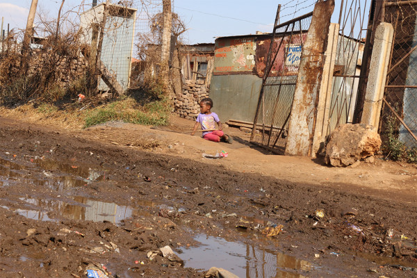 Sewerage: a little girl sits on the dusty roads with waste that has leaked from the toilets laying in front of her. Photo: Luca Kotton