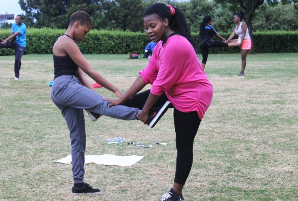 WORK IT: First year BSc student Neo Khokhone stretches her work out partner during bootcamp. Photo: Ilanit Chernick