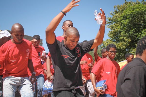 """MARCH ON: """"Freshmen"""" sing and dance as part of their first year initiation during O-week.                Photo: Roxanne Joseph"""