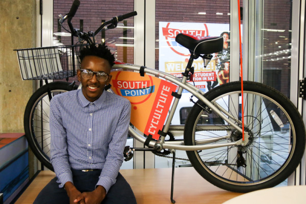South Point Marketing Intern Junior Mahlangu sitting in front of one of the bikes being given away on thursday afternoon.