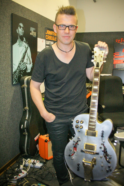 """HACKED EQUIPMENT: The """"cyber-guitarist"""" Jonathan Crossley stands with his heavily modified Ibanez guitar that he will play at the 3 cities concert in the Great Hall on 28 April. Photo: Reuven Blignault."""