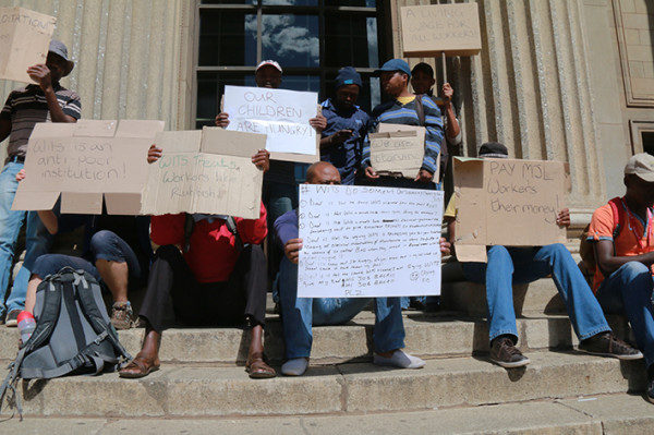 SILENT STEP: MJL Electrical workers Sello Rampypedi, Kagiso Mokotedi, Samuel Mosia, Ben Lebese, Shadrach Baloyi, Forgive Mahlaugu and Tshifhiwa Matamela sat silently on the great hall steps before the meeting began.