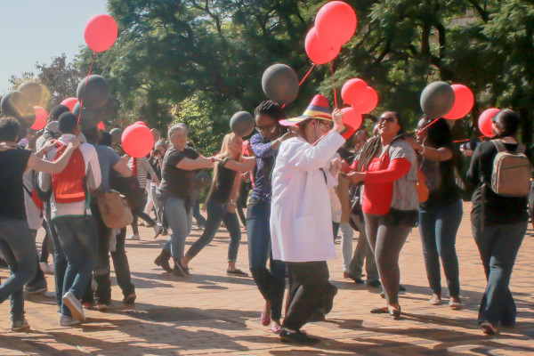 CONGA LINE: As part of a flash mob medical students form two separate conga lines dancing and holding balloons from the East campus library lawns to the Great Hall.          Photo: Dana Da Silva
