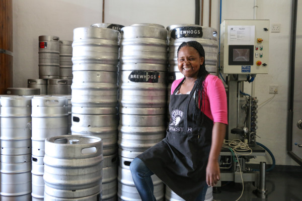 CRAFT BEER QUEEN: Apiwe Nxusani laughs as she poses with the kegs of craft beer she makes. Photo: Samantha Camara