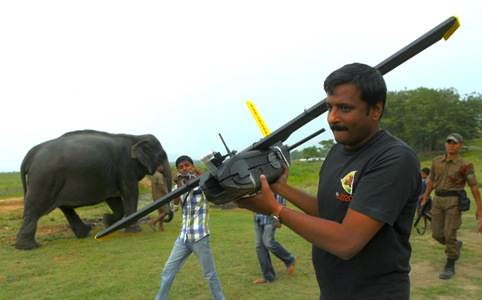 A mahout walks past with an elephant used for tourist rides as a World Wide Fund for Nature (WWF) official carries an unmanned aircraft or drone before flying them at the Kaziranga National Park at Kaziranga in Assam state, India, Monday, April 8, 2013.Wildlife authorities used drones on Monday for aerial surveillance of the sprawling natural game park in northeastern India to protect the one-horned rhinoceros from armed poachers. The drones will be flown at regular intervals to prevent rampant poaching in the park located in the remote Indian state of Assam. The drones are equipped with cameras and will be monitored by security guards, who find it difficult to guard the whole 480-square kilometer (185-square mile) reserve. (AP Photo/Anupam Nath)