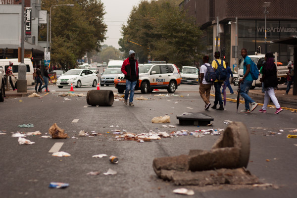 CHAOS IN THE STREETS: Pedestrians navigate their way through the debris left after the Pikitup workers strike this morning. Photo: Kyle Oberholzer