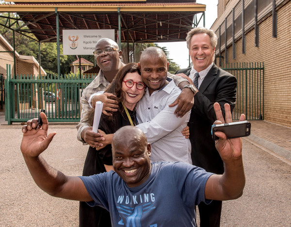 FREE AT LAST: Victor Moyo (back left) and Sampie Khanye (middle centre) are congratulated by Carolyn Raphaely, Egon Oswald and Thembekile Molaudzi (front). Photo: Roz Berzen
