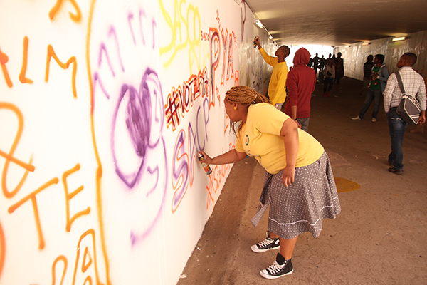 COLOURED SLOGANS: PYA candidate spray paints the tunnel. Photo: Caro Malherbe