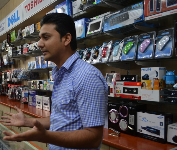 Waleed Teriq talking politics and mobile technology with customers at his new home and business, Celltronic Express.