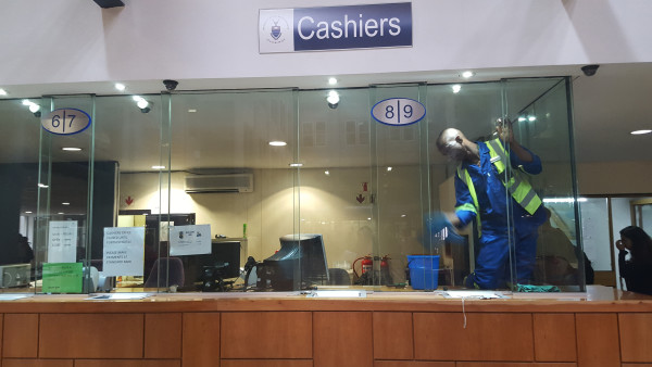 RESTORING ORDER: Cleaning staff is trying to ensure that the fees office is in operational condition by Wednesday. Photo: Nozipho Mpanza