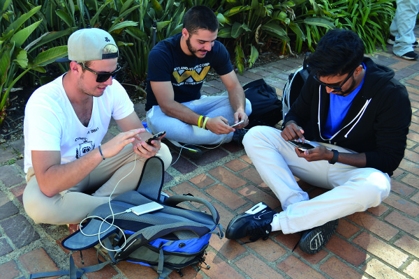 POKÉMON POWER: Students sit outside the Great Hall to play the game and power up.