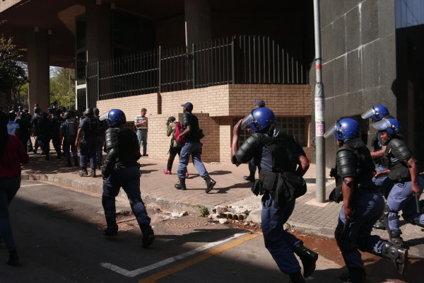 SERVE AND PROTECT: Policemen running to guard the entrance to Cosatu House from protesters. Photo: Nasya Smith