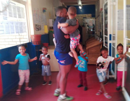 Beasts on the field, teddy bears at heart: A Wits rugby player plays with children of Othandweni.
