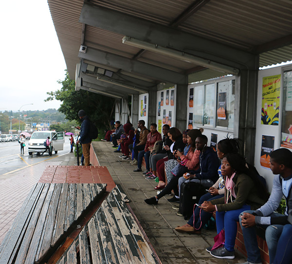 Wits students wait for the bus in rainy weather.